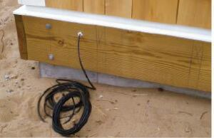 Figure 3. The author usually pulls the speaker wire through a hole drilled in the ledger before the deck is framed and leaves a long length coiled and ready to be run to the speaker locations.