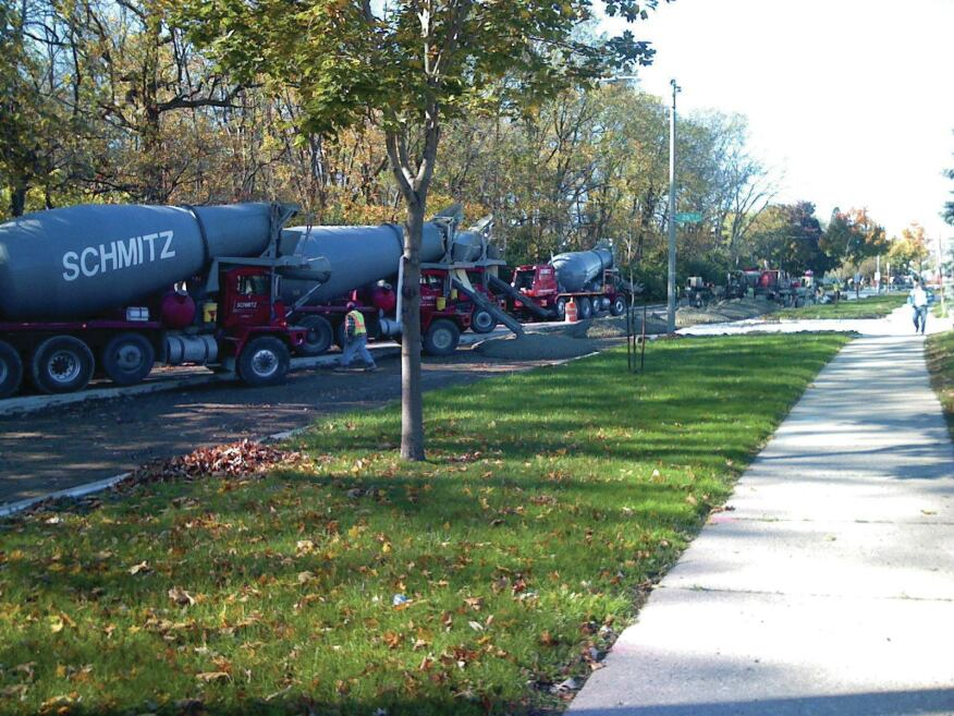 A row of Schmitz Ready Mix trucks lines up for loading at a limited-access city paving job in Milwaukee.