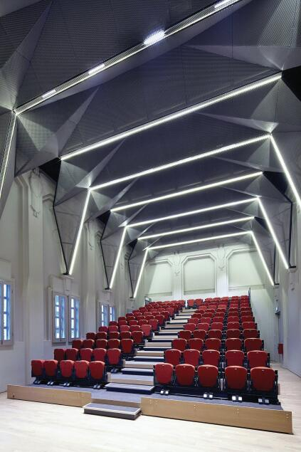 Pleated mesh screens by SCDA Architects clad the ceiling of the auditorium, which was formerly a chapel.