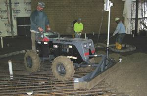 Applying this powered, laser-guided machine to the initial leveling of the dumped fresh concrete saves a lot of backbreaking labor and brings the material to within ¼ inch of the desired grade. The operator rides standing on the back of the machine.