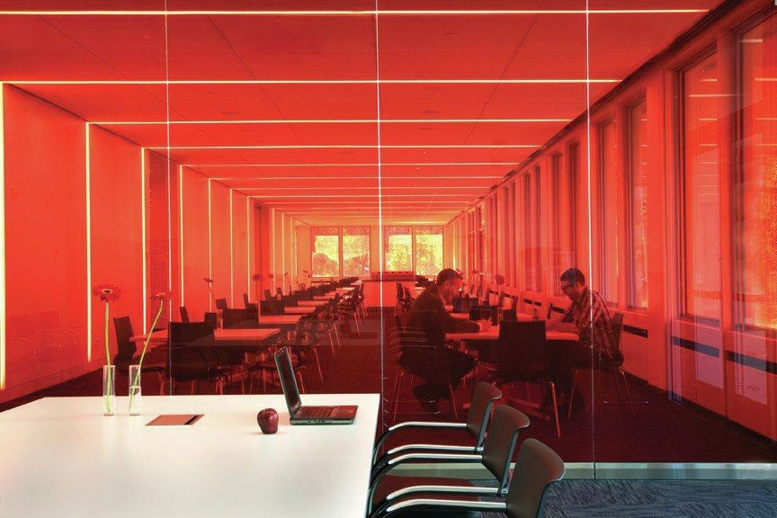 A red glass wall separates the dining area and a conference room.