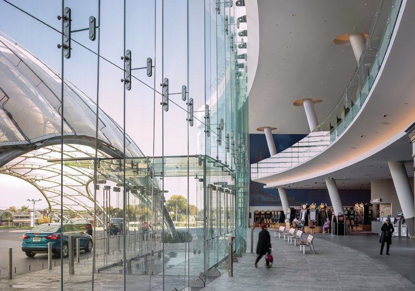 An LED cove inside the entry area highlights the curvature of the glass façade and provides indirect lighting.
