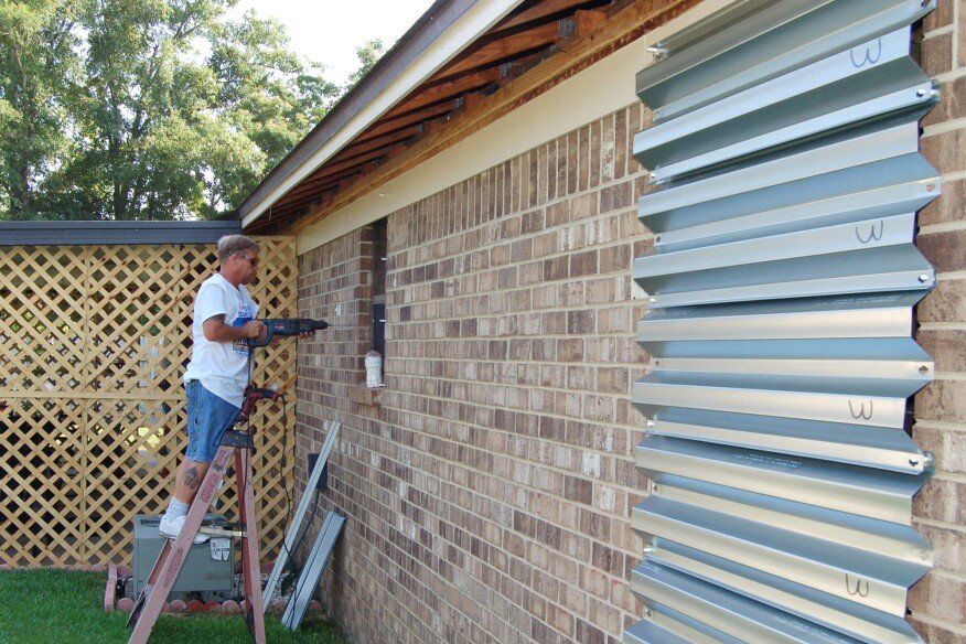 A worker installs corrugated steel shutters over windows of a Florida residence.