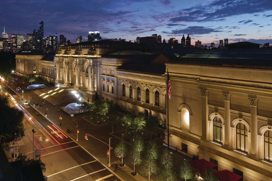 A nighttime view of the Metropolitan Museum of Art façade and plaza with the New York City skyline in the background.