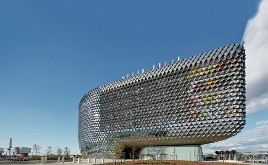 Behind the metal-and-glass west face of the new SAHMRI complex in Adelaide, Australia, brightly painted and enclosed support spaces add visual punch and reduce heat gain.