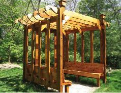 Decorative purlins cast shade on built-in benches in this western red cedar pergola by Custom Outdoor Structures, Dayton, Ohio.