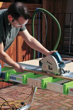 Having positioned the stock with the cut line over the recessed part of the crossbars, the author rips it without fear of cutting into the surface below. The recesses can also be used as stops when cross-cutting narrow material with a hand-held saw.