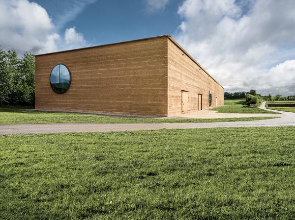 Rammed-earth walls support Ricola's new herb center in Laufen, Switzerland.