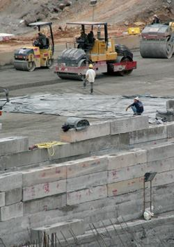 Each 30-centimeter-thick layer receives two to four passes by the articulated tandem rollers.