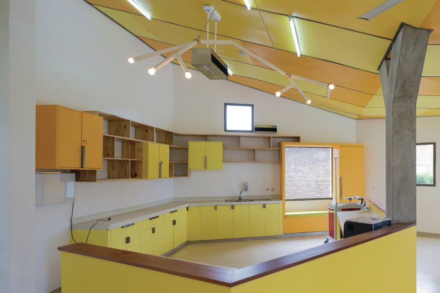 Inside the infusion room, which is the center's largest space, custom millwork and a nurse's station are all painted in vivid yellow shades from Ameki Color. A custom light fixture hangs from the steel frame and painted plywood ceiling.