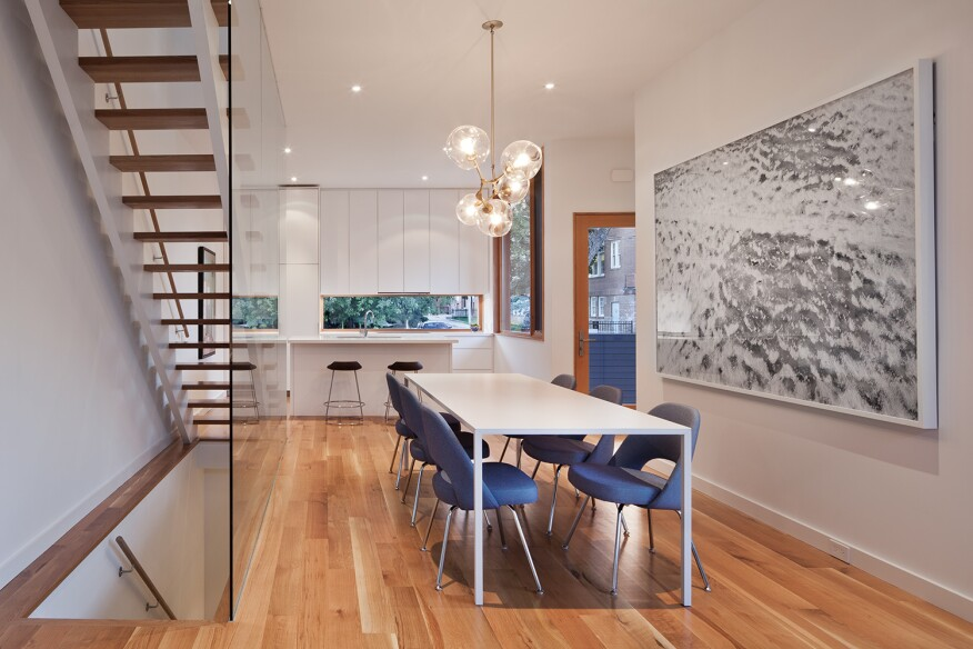The main floor features an open kitchen with Caesarstone countertops and cabinets by Catfish Design/Build. The white oak flooring continues into the dining area and the living spaces upstairs.
