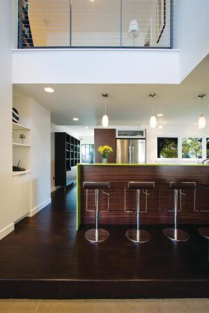 The home's interiors reflect the contemporary exterior aesthetic, with salvaged oak flooring, reconstituted wood veneer cabinetry, and recycled glass terrazzo countertops.