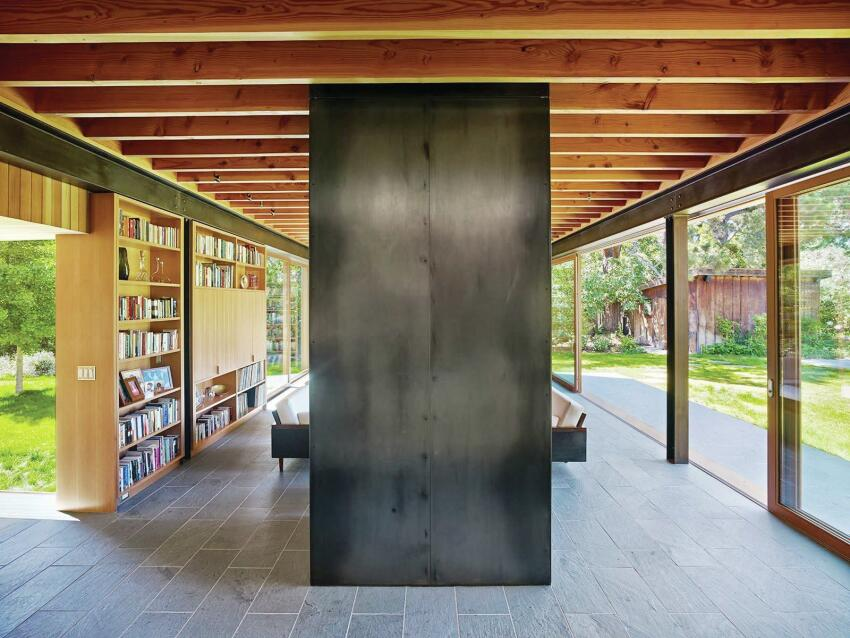 The chimney is clad in hot-rolled steel, matching the exposed structural beams.