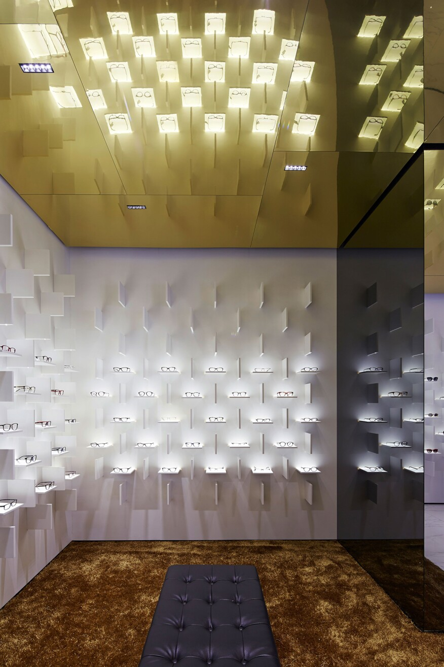 The gold-toned ceiling and the  gold-hued carpet provide a contrast to the white backdrop of the main eyewear displays.