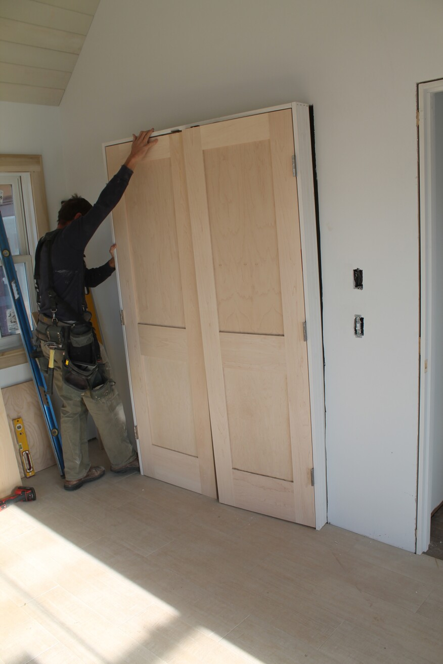 As with a single door, set the door in the opening—this time with the temporary fasteners removed.