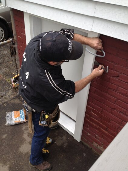 The trim compensates for the out-of-plumb foundation, leaving a space behind the trim at the top of the door. Foam backer rod is inserted into the gap before caulking is applied around the perimeter of the trim.