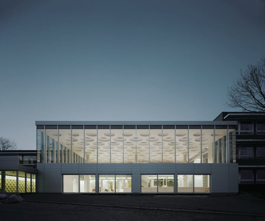 """The exterior incorporates an aluminum rainscreen from Kalzip and a curtainwall from Schüco. Ecker describes the existing 11-building, 1960s complex as """"well-built, but quiet,"""" in an aesthetic worth respecting. """"We found that we could reinterpret that on the outside,"""" Ecker says. Visible through the high-efficiency glass from Glas Trösch is the main assembly hall and its three rotationally cast concrete columns that support the mass of the concrete ceiling."""