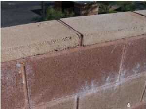 Reflected UV rays caused excessive expansion of this concrete masonry unit, which led to debonding of the coping from the bed mortar joint and debonding of coping head joints. Moisture  intrusion is the result. Note the efflorescence.