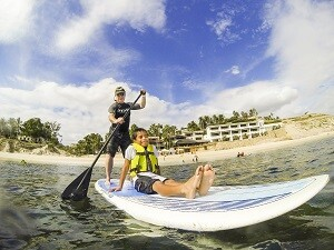 A Casa Hogar resident accompanies Dust Control Technology CEO Edwin Peterson for some stand-up paddle boarding.