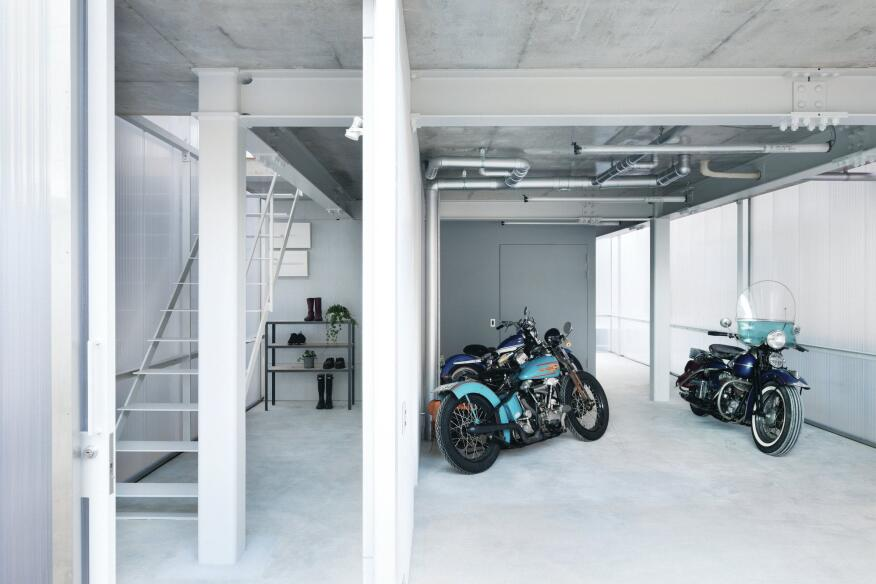 The pocket garage door and sliding front door open the façade at the ground level, revealing the stairway to the main living area and space for up to eight motorcycles.