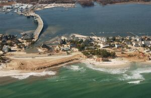 Ed Wright's house sits at the center of this NOAA aerial photo surrounded by water and sand, where crews are rebuilding the washed-away portions of the barrier island breached by Hurricane Sandy in Mantaloking. Wright's house, elevated on pilings, survived virtually intact while neighboring homes were completely destroyed.