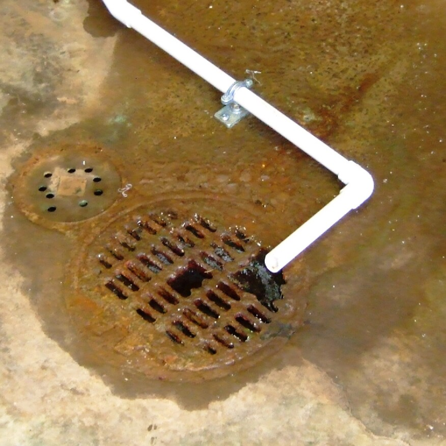 Acidic concentrate directed into a basement floor drain has eaten away the drain's brass grille. Under the floor, the condensate could be attacking cast-iron drain pipes or reinforced concrete.