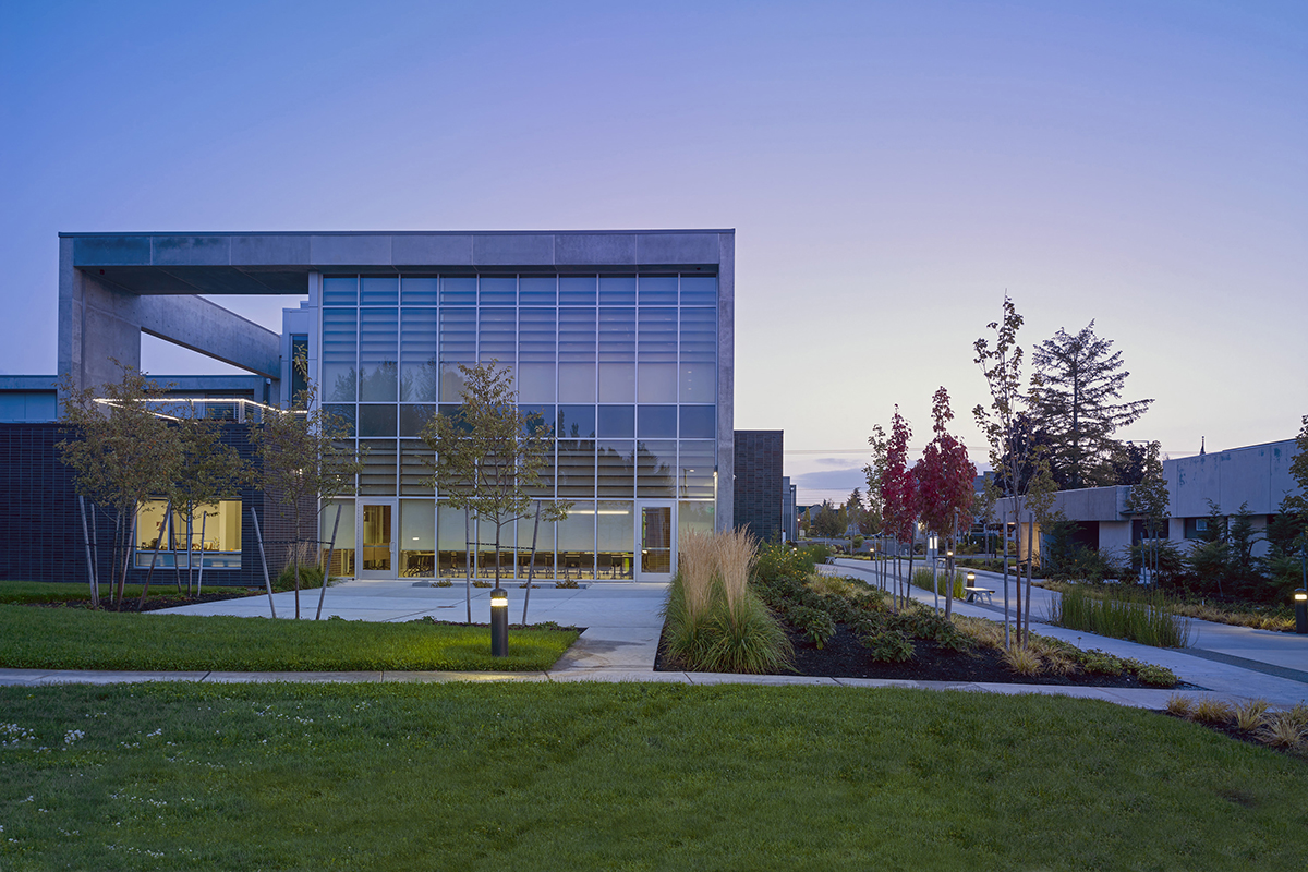 The Bates Technical College campus in the early morning or late evening. A concrete and glass building is framed overhead by a blue and yellow sky, and surrounded by sidewalks, green grass, and small trees with red and yellow leaves.