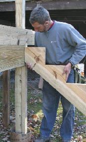 The Author Installs A Structural Header And Support Posts For Stair Continue Through Deck Frame To Guardrail System