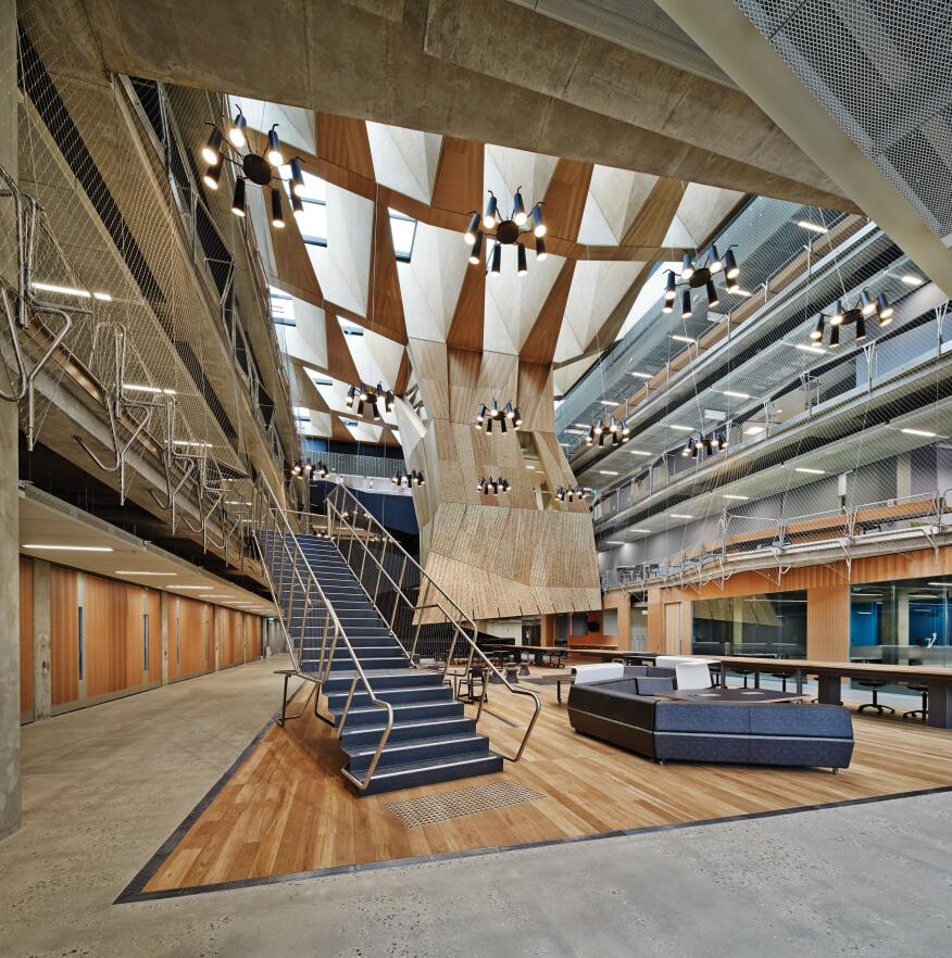 The atrium features a faceted wooden structure called the Suspended Studio.