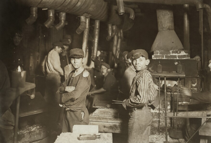 """Photos by Lewis Hine, including """"Glassworks. Midnight."""" (shown here), drew attention to child labor in industry at the turn of the last century and set in motion radical education reforms. What often gets lost in the reaction to the unsafe and unhealthy working conditions for children, is the effective transfer of knowledge from one generation to the next. The active involvement of children working with their parents and relatives is what kept craft alive in the late 19th and early 20th centuries. (Library of Congress)"""