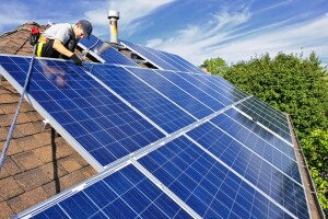 man working on solar panels on a roof