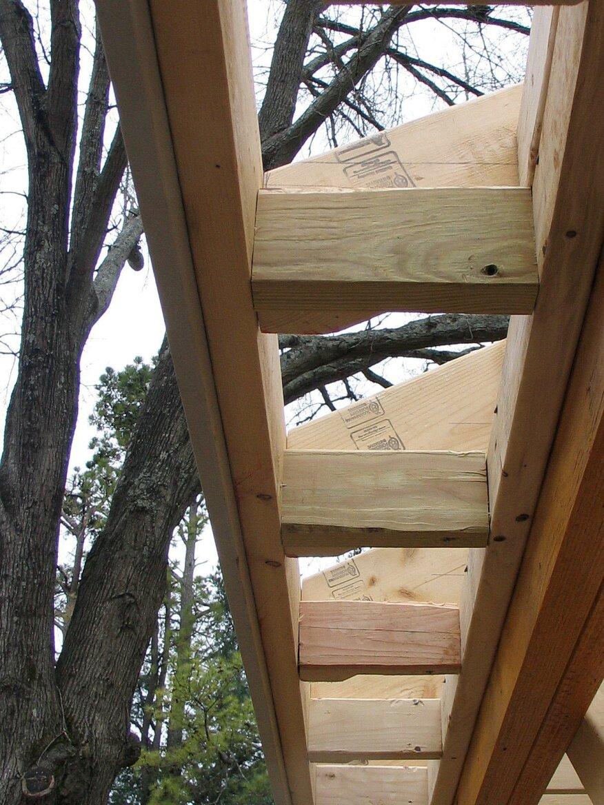 Des blocs fabriqués à partir de 2x4 se fixent à la subfascia et au ledger pour supporter le matériau de soffite et l'évent de soffite.