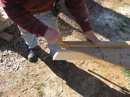 Pour le point long inférieur de la plaque du pignon, marquez l'angle d'inclinaison sur une extrémité en utilisant le gabarit de chevron. Équerrez le bois et marquez les deux bords.
