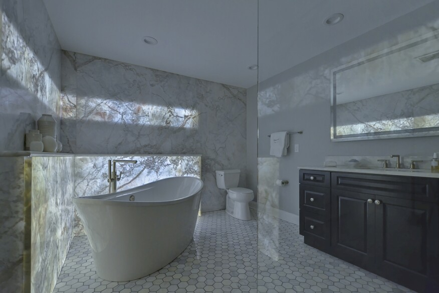 A Backlit Marble Wall Gives This Guest Bath Its 'Wow