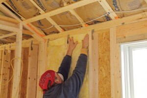 To insulate effectively, fiberglass batts need to fill the entire stud bay without being compressed. To insulate a wall, start by filling the full-width bays. Insert the batt from the top down, pushing it up against the wall plates. If the sides snag on rough lumber, run a putty knife along the side of the stud.