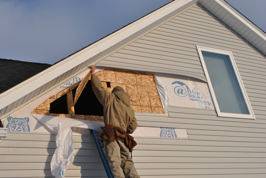 working from outside, a carpenter cuts into unheated space above the garage  next to the