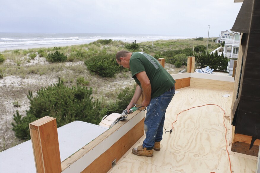 In addition to covering the subfloor with smooth 1/2-inch AC plywood underlayment, the crew eased the edges of the parapet wall with a grinder to prep the deck for the fiberglass contractor.