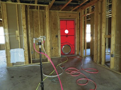 While a blower door pressurizes the house, emitter nozzles pump a fog of acrylic sealant into the building air. Walls can be exposed sheathing or finished with drywall.
