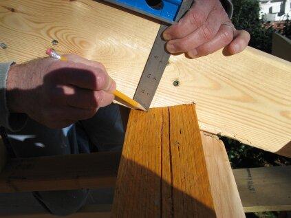 Pour trouver les points longs de la plaque inférieure du pignon abaissé, réglez une équerre à 5 pouces (3 1/2 pouces pour les belvédères et 1 1/2 pouce pour la plaque supérieure). Faites glisser l'équerre le long du chevron et marquez l'endroit où elle touche le haut du mur.
