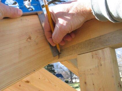 Au sommet du chevron, faites glisser l'équerre jusqu'au faîte et marquez où la lame touche.