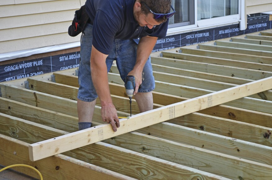 Before Installing The Mid Span Blocking He Lays A Straight 2x4 On Edge Across Deck And Perpendicular To Joists
