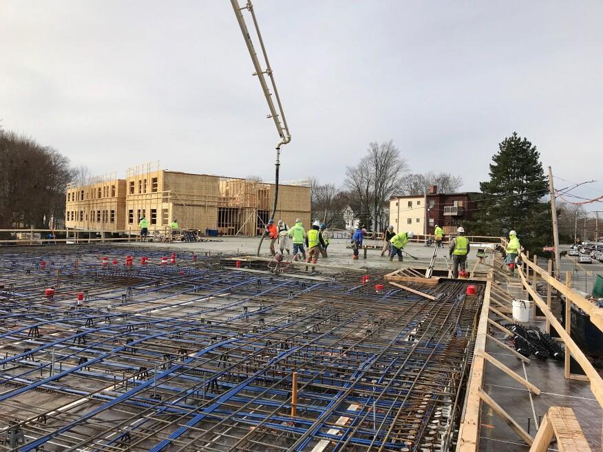 木匠在混凝土工作后面竖立建筑物的木框架部分。
