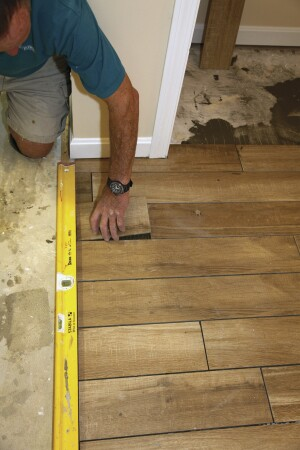 Then install the tile using a straightedge to keep the edge of the tiles in a