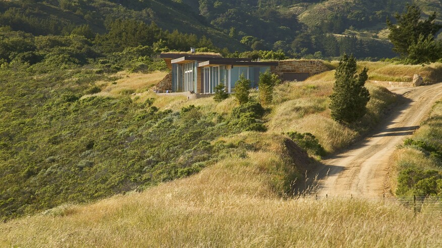 En utilisant un toit vert et en enterrant des réservoirs d'eau et de propane dans une maison souterraine, Schicketanz a conservé une vue imprenable sur l'océan Pacifique environnant.