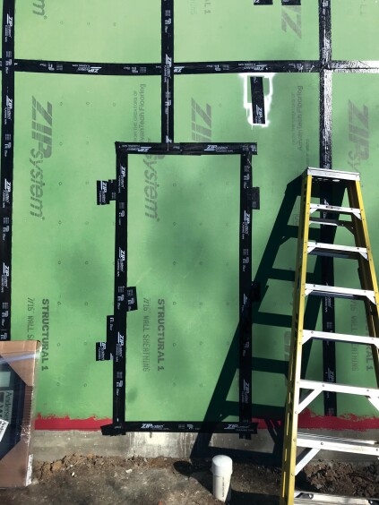 When the frame is  complete, they'll come back, fill in doors they left open for access, and run their initial blower-door test. Note the white spray  paint above the door. All temporary nailers are painted white for easy identification so they can be filled prior to the test.