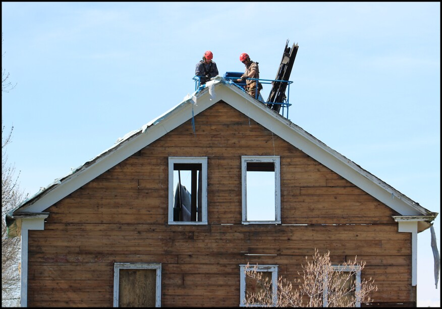 Although the roof was covered by four layers of asphalt shingles, two tarps and two layers of underlayment paper, it still leaked, causing the bulk of the damage to the home's structure. Here, the roof sheathing and shingles are removed in small sections from the lift.