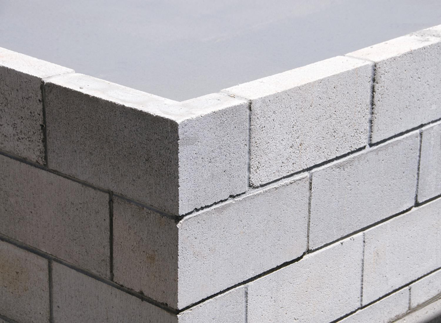 When to begin block construction on a slab edge concrete for Cinder block house construction